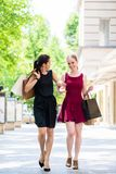 Dos mujeres hermosas que buscan boutiques de la moda durante compras Imagenes de archivo