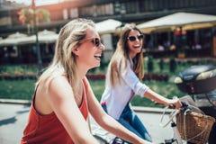 Dos mujeres hermosas que hacen compras en la bici imagen de archivo