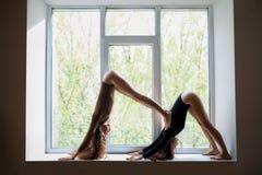 Dos mujeres hermosas que hacen el perro hacia abajo del doble del asana de la yoga en el viento Fotografía de archivo libre de regalías