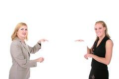 Dos mujeres hermosas que llevan a cabo la muestra en blanco 1 imagen de archivo libre de regalías