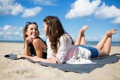 Dos mujeres hermosas que mienten en la playa que habla y que ríe Foto de archivo libre de regalías