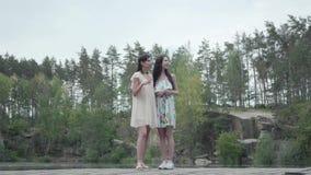 Dos mujeres hermosas que se colocan, hablando, sonriendo r visi?n espectacular almacen de video