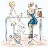 Dos mujeres hermosas que se sientan en cóctel y vino de consumición del café Imagen de archivo libre de regalías