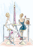 Dos mujeres hermosas que se sientan en cóctel y vino de consumición del café miran la torre Eiffel, París Fotos de archivo