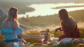 Dos mujeres hermosas que se sientan en el campo y que tienen una comida campestre - disfrutar de una vista del río en puesta del  almacen de video