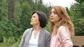 Dos mujeres, joven y mayor, están mirando en la distancia y están hablando contra el contexto de montañas y almacen de video