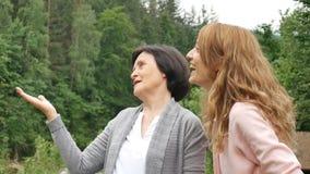 Dos mujeres, joven y mayor, están mirando en la distancia y están hablando contra el contexto de montañas y almacen de metraje de vídeo