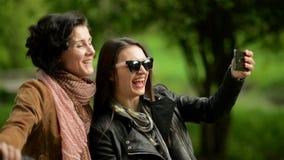 Dos mujeres jovenes activas con las bicicletas están haciendo Selfie usando el teléfono móvil Al aire libre retrato de morenitas  almacen de metraje de vídeo