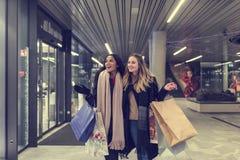 Dos mujeres jovenes adolescentes lindas que hacen compras en una tarde fría del invierno, mientras que sostiene los panieres gran Imagen de archivo
