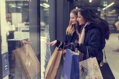 Dos mujeres jovenes adolescentes lindas que hacen compras en una tarde fría del invierno, mientras que sostiene los panieres gran Fotos de archivo libres de regalías