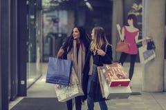 Dos mujeres jovenes adolescentes lindas que hacen compras en una tarde fría del invierno, mientras que sostiene los panieres gran Fotografía de archivo