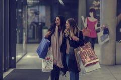 Dos mujeres jovenes adolescentes lindas que hacen compras en una tarde fría del invierno, mientras que sostiene los panieres gran Foto de archivo libre de regalías