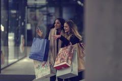 Dos mujeres jovenes adolescentes lindas que hacen compras en una tarde fría del invierno, mientras que sostiene los panieres gran Fotografía de archivo libre de regalías