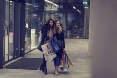 Dos mujeres jovenes adolescentes lindas que hacen compras en una tarde fría del invierno, mientras que sostiene los panieres gran Imágenes de archivo libres de regalías