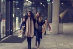 Dos mujeres jovenes adolescentes lindas que hacen compras en una tarde fría del invierno, mientras que sostiene los panieres gran Fotos de archivo