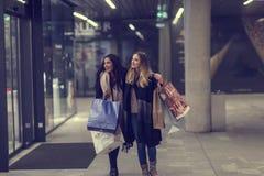 Dos mujeres jovenes adolescentes lindas que hacen compras en una tarde fría del invierno, mientras que sostiene los panieres gran Imagen de archivo libre de regalías