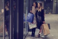 Dos mujeres jovenes adolescentes lindas que hacen compras en una tarde fría del invierno, mientras que sostiene los panieres gran Imagenes de archivo
