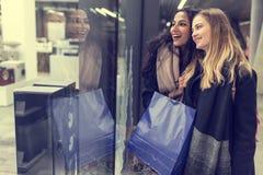 Dos mujeres jovenes adolescentes lindas que hacen compras en una tarde fría del invierno, mientras que sostiene los panieres gran Foto de archivo