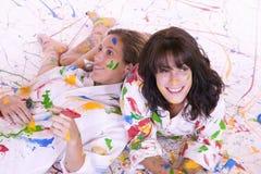 Dos mujeres jovenes atractivas cubiertas en pintura colorida fotografía de archivo libre de regalías