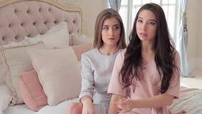 Dos mujeres jovenes atractivas en elegancia visten el planteamiento de sentarse en cama almacen de metraje de vídeo