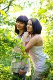 Dos mujeres jovenes atractivas que presentan en un verano parquean Imagen de archivo libre de regalías