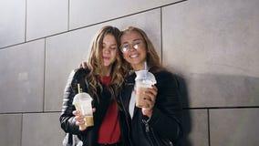 Dos mujeres jovenes atractivas que sostienen los cócteles fríos y que presentan cerca de la pared gris del edificio moderno en ve almacen de metraje de vídeo