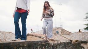 Dos mujeres jovenes caminan en una cerca del ladrillo almacen de video
