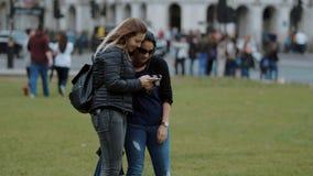 Dos mujeres jovenes comen el helado - hielo suave almacen de metraje de vídeo