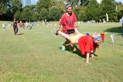 Dos mujeres jovenes compiten en raza de la carretilla en la recaudador de fondos del verano imagen de archivo libre de regalías