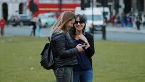 Dos mujeres jovenes comprueban las fotos en la cámara - Londres que hacen turismo en la cámara lenta almacen de metraje de vídeo
