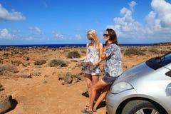 Dos mujeres jovenes con el coche miran el mapa de camino Fotografía de archivo