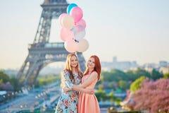 Dos mujeres jovenes con el manojo de globos en París cerca de la torre Eiffel Foto de archivo libre de regalías