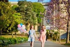 Dos mujeres jovenes con el manojo de globos en París en un día de primavera Imagenes de archivo