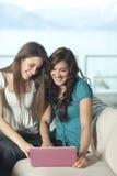 Dos mujeres jovenes con el ordenador Foto de archivo libre de regalías