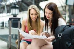 Dos mujeres jovenes con equipaje y el mapa Imágenes de archivo libres de regalías