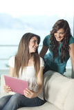 Dos mujeres jovenes con la computadora portátil Foto de archivo