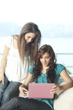 Dos mujeres jovenes con la computadora portátil Imagen de archivo libre de regalías