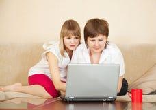 Dos mujeres jovenes con la computadora portátil Foto de archivo libre de regalías