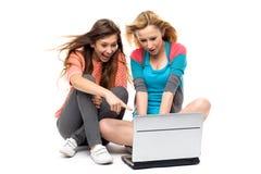 Dos mujeres jovenes con la computadora portátil Fotos de archivo