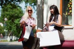 Dos mujeres jovenes con los bolsos de compras. Imágenes de archivo libres de regalías