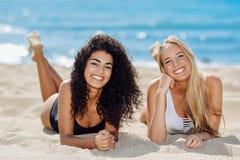 Dos mujeres jovenes con los cuerpos hermosos en traje de ba?o en una playa tropical imagenes de archivo