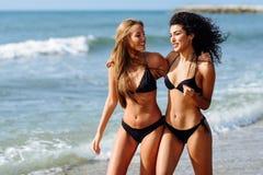 Dos mujeres jovenes con los cuerpos hermosos en traje de ba?o en una playa tropical imagen de archivo