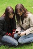 Dos mujeres jovenes con un teléfono móvil Imagen de archivo libre de regalías
