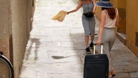 Dos mujeres jovenes corren hacia fuera de a la vuelta de la esquina y caminan abajo del callejón almacen de metraje de vídeo