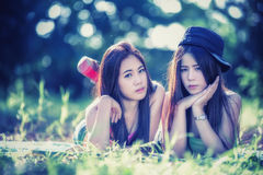 Dos mujeres jovenes de Asia que mienten en hierba Imagen de archivo