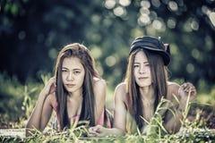 Dos mujeres jovenes de Asia que mienten en hierba Fotos de archivo libres de regalías