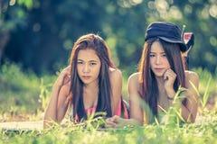 Dos mujeres jovenes de Asia que mienten en hierba Imagenes de archivo