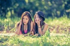 Dos mujeres jovenes de Asia que mienten en hierba Foto de archivo