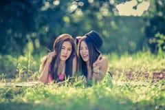 Dos mujeres jovenes de Asia que mienten en hierba Imagen de archivo libre de regalías