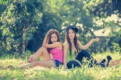Dos mujeres jovenes de Asia que se sientan en hierba Fotografía de archivo